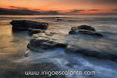 Golden sunset (Iigo Escalante) Tags: blue sunset sea sky espaa orange costa sun black sol water vertical azul stone clouds landscape atardecer golden coast mar spain agua rocks waves negro silk paisaje national shore cielo nubes reflejo planet conde lonely fotografia seashore naranja olas bizkaia seda vasco euskadi geographic vizcaya rocas pais norte nast dorado piedras traveler cantabrico cantabric iigoescalante