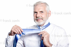 man senior getting dressed tying windsor necktie (Franck Camhi) Tags: portrait people white man france detail male senior smiling businessman closeup shirt cutout person one 1 clothing handsome tie knot clothes business whitebackground mature dressingup friendly casual studioshot lesson adjusting executive bearded preparation necktie prepare tying caucasian grayhair greyhair 60years gettingdressed 50years lookingatcamera windsorknot