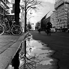 Berlin - street (Anton C.) Tags: analoguephotography adofix adox adoxadonal analogue analog berlin bw blackwhite black white blackandwhite blanconegro bronica monochrome film filmisnotdead germany ishootfilm kodak kodaktrix mitte mediumformat mittelformat nikkor bike square rodinal streetphotography streetlife standdevelopement semistand selfdeveloped reflection water curb puddle tree tower 120 6x6 zenzabronicas2a zenzabronica rollfilm tx400