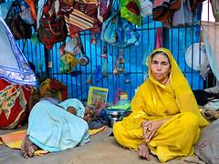 Yellow and Blue (Dick Verton) Tags: travel blue people woman india yellow temple asia sitting sit varanasi seated pilgrims dickverton