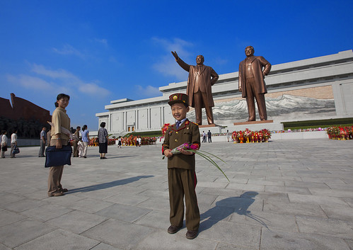Kid In Army Uniform Paying Respect To The Two Statues Of The Dear Leaders In Grand Monument Of Mansu Hill, Pyongyang, North Korea