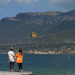 Mother and daughter enjoying impressive Lago di Garda (Bn) Tags: park blue summer vacation sky italy holiday mountains colour water weather sport rock del clouds swimming landscape fun lago coast carved topf50 garda mediterranean italia waves sailing wind unique air kitesurfing mount di windsurfing fjord relaxation shape majestic climate malcesine gem turbulence gardameer lakegarda dis