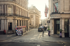 Trafalgar (Adam Haranghy) Tags: street red england sun sunlight news man building london yellow stone architecture booth square jack person photography gold mercedes hotel licht newspaper fuji britain flag union great trafalgar scene cobble jacket van minivan zeitung gegenlicht ldn kopfsteinpflaster x100 zeitungsstand grosbritannien