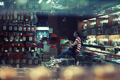 Through The Shelves Of The Medicine Shop (Jon Siegel) Tags: woman shop night 50mm lights evening nikon singapore chinatown sitting bottles traditional chinese medicine nikkor tcm shelves f12 singaporean nikkor50mmf12ais d700