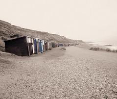 (Khadijah Turner) Tags: sea england beach rocks waves gloomy pebbles calm huts bartononsea