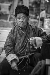 Bhutanese Man Portrait. (Tapas Ghosh Photography) Tags: blackwhite portrait streetphotography bhutan bhutanese face man oldage pray buddhism buddhist travelphotography tradition cultural dress