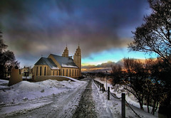 Akureyrarkirkja at Sunset in Iceland (` Toshio ') Tags: blue trees winter sunset snow storm cold building ice architecture clouds iceland europe european cloudy path gray freezing stormy akureyri akureyrarkirkja toshio lutheranchurch thechurchofakureyri