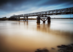 Turning tide (Explored) (Steven Docwra) Tags: longexposure bridge sky colour water clouds river suffolk weed crossing footbridge harbour pipeline southwold rivercrossing walberswick southwoldbridge walberswickbridge