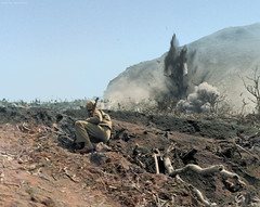 US Marine watches as Japanese forces are shelled on Iwo Jima, ca. Feb-Mar 1945. (Jared Enos) Tags: world war ii wwii iwo jima battle pacific theater us marines explosion shell artillery usa japanese japan history historic colorization colorized