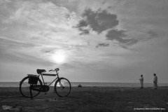 The Journey (Praphul.T.) Tags: ocean sunset sea two people blackandwhite sun white black art tourism monochrome clouds canon photography eos dramatic kerala calm journey cycle 1855mm prayers irinjalakuda canon550d moonupeedikabeach