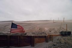 Whipping Sand (inafreeland) Tags: storm film march newjersey sand wind flag nj americanflag lbi longbeachisland jerseyshore noreaster canoneoselan7e kodakektar100