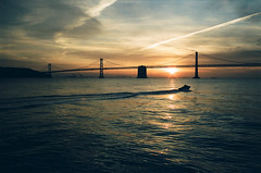 Bay Bridge Sunrise (carloparducho) Tags: ocean sanfrancisco sunset sky seascape film beach water silhouette backlight clouds oakland boat lomo lomography waves 28mm olympus filter baybridge bayarea backlit watersports polarizer omg zuiko om20 polarizingfilter