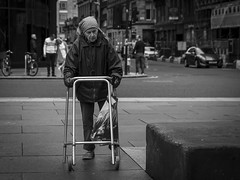 A Steadfast Footing (Leanne Boulton) Tags: monochrome urban street candid portrait streetphotography candidstreetphotography streetlife sociallandscape old age aged elderly woman female face facial expression mobility walking frame zimmer disability determination struggle tone texture detail depthoffield bokeh natural outdoor light shade shadow city scene human life living humanity people society culture canon 7d 50mm black white blackwhite bw mono blackandwhite glasgow scotland uk