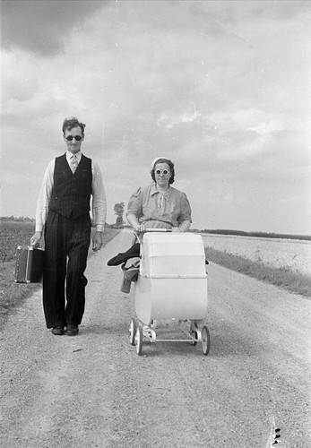 Statarpar med resväska och barnvagn på hemväg från semestern.