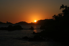 Sun setting in Acapulco (lynne_b) Tags: ocean trees light sunset sea sky sun mountains reflection beach water silhouette landscape mexico evening twilight rocks boulders palmtrees pacificocean acapulco tropical heavens settingsun acapulcobay
