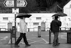 Only another 520 Yards........ (Clive Jones Photography) Tags: people urban streets monochrome streetphotography isleofwight umbrellas blackandwhitephotography urbanphotography nikond300 clivejones theoxonian sigmaf1450mmlens