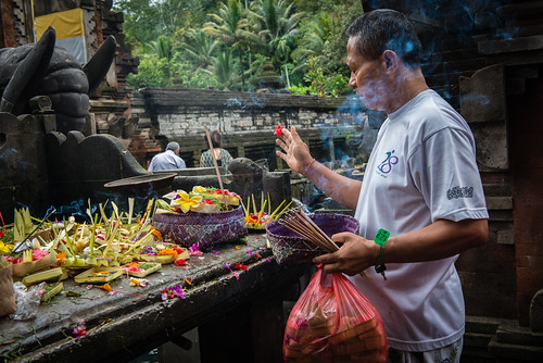 A visitor makes floral and inscence offerings at Pura Turta Empul