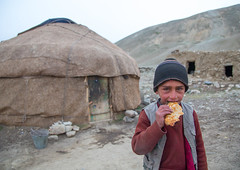 Wakhi nomad boy eating bread in front of his yurt, Big pamir, Wakhan, Afghanistan (Eric Lafforgue) Tags: 67years afghan afghan317 afghani afghanistan badakhshan bigpamir bread centralasia child childhood childrenonly cold colourimage community cultures food frontview horizontal indigenousculture ismaili lifestyles lookingatcamera males malongzan nomad nomadicpeople oneboyonly onechildonly oneperson outdoors people photography portrait traditionalclothing waistup wakhancorridor wakhi yurt wakhan pamir