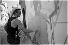 (Valencia Spain) Graffiti artist to work by spraying from a wall.© RESPECT the copyright. (YoLeenders) Tags: blackandwhite españa art graffiti artist streetphotography rangefinder urbanite analoog nikonsupercoolscan5000ed valenciacentro delta100asa elmaritm12821mmasph developerid11ilford11 leicam6ttl075