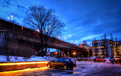 Cars by the Bridge (henriksundholm.com) Tags: city bridge snow reflection tree cars ice car sign clouds buildings puddle lights parkinglot sweden stockholm sdermalm dusk bridges sverige lamps hdr gravel skanstull skanstullsbron hlens skansbron