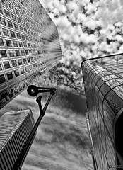 Looking up @ Canary Wharf photo (david.kittos) Tags: blackandwhite bw reflection building london architecture clouds plane canarywharf glassbuilding zd 1260mm olympusmagazine