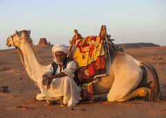 Man And His Camel In Front Of The Pyramids And Tombs In Royal Cemetery, Meroe, Sudan (Eric Lafforgue) Tags: africa travel sky brown men history tourism archaeology nature cemetery horizontal architecture outdoors photography death sand memorial day sitting desert pyramid northafrica soedan sudan tomb tranquility unescoworldheritagesite camel transportation custom sanddune ancientcivilization khartoum nubia royalty thepast adultsonly scenics oneperson soudan tranquilscene saharadesert northernafrica meroe traditionalclothing realpeople traveldestinations colorimage naturalpattern lookingatcamera beautyinnature jalabiya buildingexterior fulllenght merowe onemanonly aridclimate  1people szudn sudo  builtstructure northernsudan pyramidsofmeroe northsudan blackpharaohs      xuan ert7835