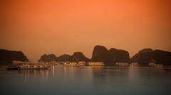 Halong Bay Ship Congregation at Sunset (DaveMWeber) Tags: ocean sunset red sky water stone canon island lights bay boat long hill scene vietnam limestone ha hanoi karst vignette 1022mm halong halongbay t2i