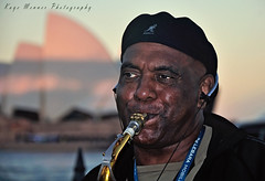 Sax in the City (Kaye Menner) Tags: city blue red portrait musician music man black face hat eyes cap instrument busker musicalinstrument operahouse brass busking saxophone woodwind muso streetmusician brassinstrument saxophoneplayer mouthpiece blackcap sydneycity woodwindinstrument manportrait portraitofaman saxinthecity manplayingsaxophone streetmuso citybusker kayemennerphotography kayemenner operahousebackground saxinthestreet kayemennerportrait