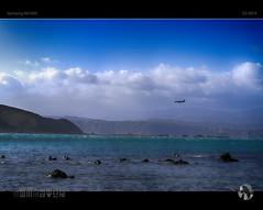 Out of the Blue (tomraven) Tags: blue bluesky bluesea clouds sky plane airplane aircraft rocks mountains cloud aravenimage tomraven q32016 samsung nx1000