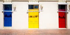 Alfredo, Maria And Nazzareno (Sean Batten) Tags: marsaxlokk malta mt blue yellow red doors nikon df 35mm town pavement