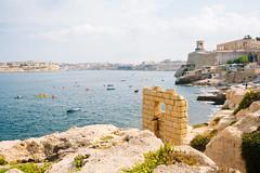 La Valletta (lorenzoviolone) Tags: cloudy d5200 dslr fujiastia100f nikon nikond5200 old reflex rocks vsco vscofilm canoe canoes cliff cliffside decay horizonontheland kayaks rowing sea seaside sky towerbell travel:malta=aug2016 wall warmemorial water valletta malta