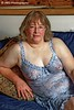 Sandra Posing in Her Sexy Blue Teddy (jgabby7) Tags: glamour lingere sexylingerie seated sofa indoors blonde shorthair mature glasses breasts