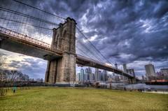 BkBridge (Slapz NYC) Tags: park nyc newyorkcity bridge urban cloud ny newyork storm grass brooklyn clouds river dark manhattan brooklynbridge eastriver hdr
