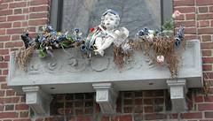 Bronx Window Box (TheMachineStops) Tags: 2005 nyc newyorkcity outdoor bronx windowbox brick angel bull flowers window cherub
