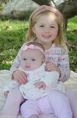 Miss E and Miss M (Kirsten Goebel Photography) Tags: family pink baby green love beautiful smile grass sisters children outdoors sister daughter warmth bow cuddle