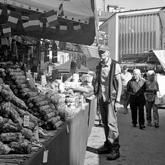 The old man and the salamis (luciano_campani) Tags: rolleiflex planar 35f kodak trix400 film 120 6x6 analog pellicola monochrome bianconero mediumformat italia italy italien domodossola street market mercato strada mercado strasenmarkt old man salami salame alte mann salamis vieil homme