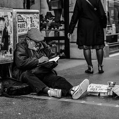 Reading helps you feel less lonely. (romainln) Tags: street streetphotography homeless reading poverty misery blackwhite blackandwhite streetlife book olympus 45mm loneliness