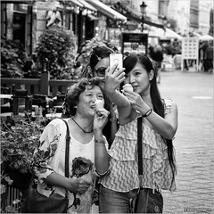 Sweeter than icecream... (John Riper) Tags: johnriper street photography straatfotografie square vierkant bw black white zwartwit mono monochrome hungary budapest candid john riper fujifilm fuji xt1 18135 young women tourists smile selfie smartphone iphone icecream terrace shopping asian girls