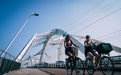 Late Summer Odyssey (Rolling Spoke) Tags: bike bicycle bici bicicleta bicicletta fahrrad fiets ciclismo velo street bridge brug pole angle view girl girls ride cycle cycling summer blue sky white ennesheermabrug ijburg amsterdam panasonic lumix gx1 f25 prime