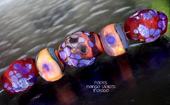 Rocks Mango Violets Frosted (Laura Blanck Openstudio) Tags: openstudio openstudiobeads glass handmade lampwork beads bead set jewerly murano big fine arts artist artisan show festival wearable pebbles stones rocks nuggets faceted transparent whimsical funky odd colorful multicolor organic earthy abstract asymmetric frit speckles made usa published winner category south miami copper green rubino maroon ruby mango orange coral maize violet grape lavender lilac purple eggplant plum mauve matte etched frosted glow opaque