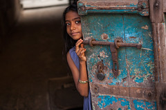Beauty. Kochi (Marji Lang) Tags: door travel blue portrait people india cute colors girl beautiful beauty face look photography kid eyes colorful child hand looking peekaboo indian young streetphotography streetportrait shy kerala hidden stare littlegirl curious lovely gaze graceful curiosity cochin meet kochi doorstep bluedoor encounter inde streetshot fortkochi fortcochin youngbeauty 2013 behindthedoor marjilang