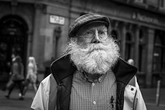 The Bush (Leanne Boulton) Tags: people monochrome urban street candid portrait portraiture streetphotography candidstreetphotography candidportrait streetlife closeup aged elderly man male face facial expression look emotion feeling eyes beard bushy cap rugged character tone texture detail depthoffield dutchangle bokeh natural outdoor light shade shadow city scene human life living humanity society culture canon 7d 50mm black white blackwhite bw mono blackandwhite glasgow scotland uk