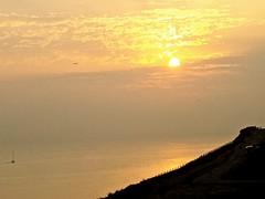 Sailing into the Setting Sun (bimbler2009) Tags: fujifilms9900w outdoor sunset landscape coast shore sky seaside sun clouds boat movement motion reflection silhouette