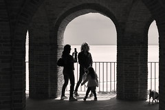 Giochi in controluce (GP Camera) Tags: nikond80 nikonafsdx1855mmf3556gvr backlight controluce people persone sea mare shot scatto arches archi architecture architettura pillars pilastri columns colonne bricks mattoni balconies balconi women donne child bambina dog cane railing ringhiera horizon orizzonte light luce shadows ombre lightandshadows lucieombre lighteffects effettidiluce summer estate holydays vacanze plays giochi monochrome monocromo bw biancoenero italy italia marche darktable gimp digitalprocessing elaborazionedigitale
