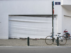 Suspended 1 (godelieve b) Tags: brussels bruxelles window shop vitrine blanc white suspended street urban mur wall bike store volet pavement noncoloursincolour