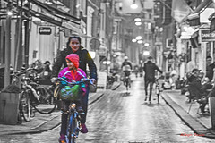 a way of life (albyn.davis) Tags: color selection selectivecolor bicycles mother child people street wet rain evening amsterdam neighborhood lights cafes restaurants pink