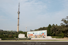 Telecommunications tower and funfair in the background and revolutionary mosaic in Pyongyang, North Korea (DPRK) (tommcshanephotography) Tags: adventure asia communism dprk democraticpeoplesrepublicofkorea expedition exploring kimilsung kimjungil kimjungun northkorea pyongyang revolution secretcompass travel trekking