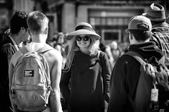 Pretty & A Smile for the Photographer (Just Ard) Tags: woman hat shades sunglasses smile people person face street photography candid unposed black white mono monochrome bw blackandwhite noiretblanc biancoenero schwarzundweis zwartwit blancoynegro  justard nikon d750 85mm