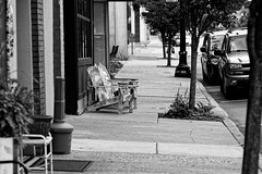 Rest (joeldinda) Tags: nikon d500 nikond500 blackandwhite bw monochrome 2016 michigan ioniacounty portland centralbusinessdistrict downtown building store commercialbuilding street tree sidewalk bench 3251 august