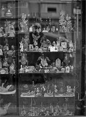 (frscspd) Tags: 75540030 20160730 pentax pentaxmx mx takumar takumar58mm 58mm ilford ilfordxp2 ilfordxp2400bw filmgrain film xp2 madrid shop shopwindow window statuette statuettes catholic reflection angel angels crosshatch pscrosshatchfilter nativity nativities marinaamongtheangels